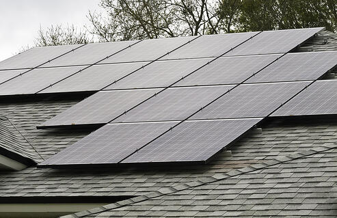 Array of solar panels on sloped roof of detached house on an overcast morning-1