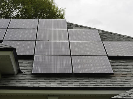 Solar panels on sloped roof of house on overcast day