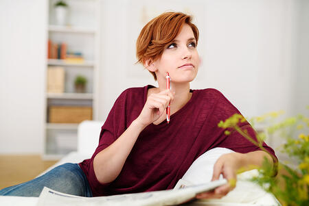 Thoughtful Attractive Young Woman Answering Crossword Puzzle Game on Newspaper at the Living Room Couch.